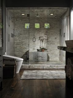 The contrast of the shower to the rest of this room is exquisite. Stunning dark wood floors showcase the beautiful display of textures of the stone and tile in the shower itself.