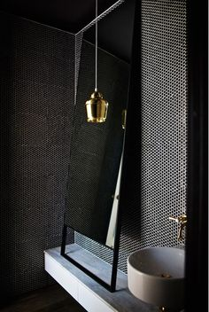 What makes this bath design is the brass contrasting against the black mosaic tile, Nice mix of textures.