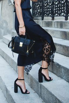 Strappy block heels and satchel paired with black lace skirt.