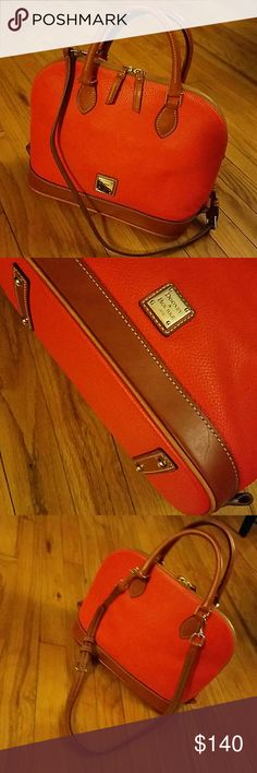 WEEKEND SALE Dooney & Bourke leather bag! Authenic Dooney&Bourke leather purse. Great burnt orange color with brown leather detailing! Full zip closure with multiple compartments inside. 13 inches across, 10 inches vertically, and 5 inches for the base. Both handle and shoulder straps. In perfect condition! Dooney & Bourke Bags Shoulder Bags