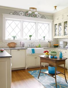 Cabinets with brushed-on milk paint, tile with a crackled ivory finish, plus honed granite and a flea-market table give this new kitchen a softly aged look.