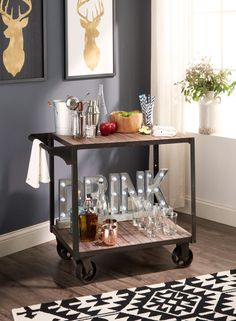 """Give your bar cart a fall refresh with the right mix of classic drinkware—think: rocks glasses and Moscow mule mugs—and a bit of personality. Featured product includes: Darlene bar cart, Privilege """"Drink"""" LED light, Food Network Moscow mule mugs and rocks glasses, Artland metal ice bucket, Cathy's Concepts 6-pc. Mixology cocktail set, SONOMA Goods for Life root wood bowl, Kaleen Habitat rug and Americanflat deer head art. Style to your cart's content with Kohl's."""
