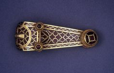 Curved gold dummy buckle or clasp of elongated triangular form. The loop is decorated with cloisonné garnet work, comprising one band of a running step-pattern, and one of plain rectangular and keystone cells. The buckle has a cut-away dummy tongue. Below the loop and 'tongue' are two prominent plain gold circular bosses qith beaded wire collars, each set with a circular cabochon garnet. These conceal rivets which connect with a back-plate of plain beaten gold. At the toe of the buckle is a…