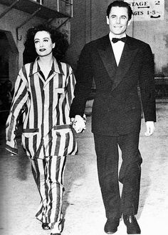 Glenn Ford and Joan Crawford walk hand in hand on the Columbia lot, March 1942. S)