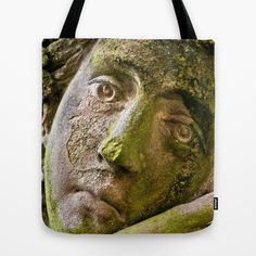 Melancholy in stone Tote Bag by Pirmin Nohr - $22.00  This is the sad looking face of an statue of an ancient greek goddess. I found it on  a beautiful cemetery, which has a lot of old graves, crypts and statues.   stone, sculpture, art, lichen, face, portrait, ancient, antique, green, sad, melancholic,  mood, sad mood, sadness, look, eyes