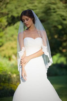 This luxurious, graceful bridal veil is sure to make your heart skip a beat! Combining a sophisticated silhouette with cascading lace trim, this veil is a one-of-a-kind masterpiece that will elevate your bridal look with its understated glamour and charm. • The bottom edge is trimmed with a scalloped lace in a beautiful floral design • There is a thin ribbon edge finish from the comb to the start of the lace • A classic fingertip length veil that is hand sewn from the most luxurious bridal…