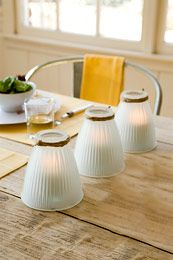 """Glass shades from a ceiling fan turned into table top votive """"holders."""" Cute idea! And you can usually find these things at yard sales/thrift stores/flea markets for cheap, cheap, cheap!"""