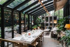 Crawford created a covered patio addition where guests can relax and enjoy a meal within the garden. The leafy glass house holds modern wood furnishings and cozy textiles.