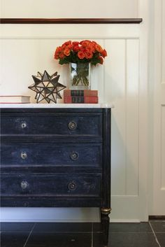 Foyer with hand distressed black chest with marble top filled with books and Moravian star.
