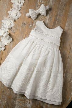 Βαπτιστικά ρούχα για κορίτσι της Maria Zeaki φόρεμα από λευκό λινό ύφασμα με υπέροχη φάσα από βαμβακερή δαντέλα και τρέσα πομ-πομ στο μπούστο