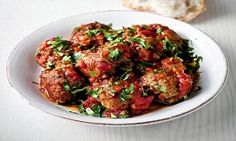 Pour the tomato sauce over the meatballs once they're lightly browned and simmer. Sprinkle with chopped parsley to serve.