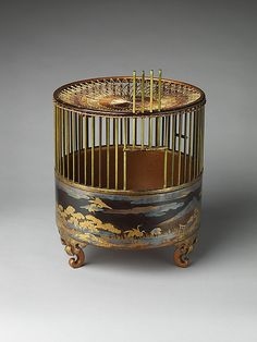 "Japanese Bird Cage - 18th C. /  Black lacquer ground with gold and silver maki-e, dyed wood, and silk netting - The cranes, wheels, and flowing poem scripts decorating this birdcage refer to both Wakanoura, an inlet on the Kii Peninsula revered as the ""bay of poetry,"" and to several famous compositions that celebrate this scenic place."