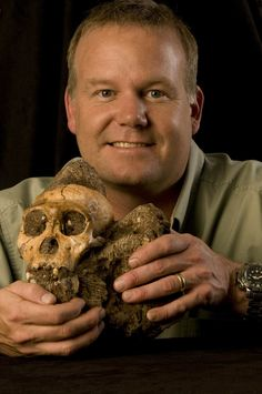 "Researcher Lee Berger holds the cranium of Australopithecus sediba — Australopithecus means ""southern ape,"" and is a group that includes the iconic fossil Lucy, while sediba means ""wellspring"" in the South African language Sotho."