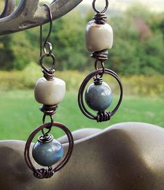 These light weight earrings were made with copper wire, wood-fired beads and porcelain beads. They are handmade from top to bottom.