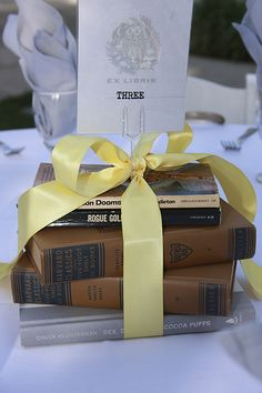 this stack is bigger and with more ribbon. A stack of books topped with flowers or photos of the couple, or topped with nothing at all, just a stack of the couple's favorite reads can be meaningful and lovely.