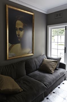Warm gray painted living room with white crown moulding, charcoal velvet sofa an.,Warm gray painted living room with white crown moulding, charcoal velvet sofa and large gold-framed oil painting. Dark Grey Couches, Grey Velvet Sofa, Dark Blue Walls, Black Sofa, White Walls, Pink Velvet, Dark Living Rooms, Living Room Paint, Living Room Sofa