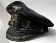 The beat-up cap of a German U-boat officer who served on U-30 or U-110. Note the little funny figurine pinned right above the visor, a routine practice among U-boat officers.