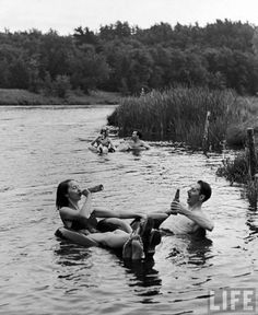 Alfred Eisenstaedt: Couple drinking beer at inner tube floating party on the Apple River. Somerset, WI, 1941