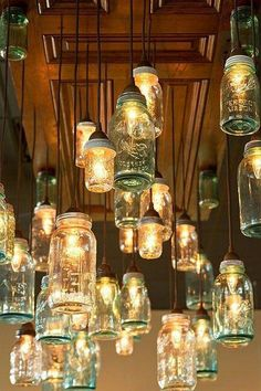 Dinning/Kitchen Area: I like this idea to give WAY more lighting to dark room! Could Wine or Soda Bottles along with Mason Jars. A whole page of jar lights, love that this picture has them hanging from an old door! Mason Jar Chandelier, Mason Jar Lighting, Mason Jar Lamp, Kitchen Lighting, Diy Chandelier, Pot Mason Diy, Mason Jar Crafts, Diy Luminaire, Deco Restaurant