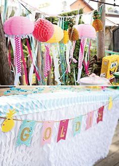 """""""The backdrop garland was made by using several enchanting ribbons adorned with spray painted gold pineapples, crepe paper, and our custom pink jellyfish. The birthday girl's name was displayed on a shimmery paper banner by using gold glitter sticker decals. The linens were custom made using store bought chiffon skirting and chevron fabric."""""""