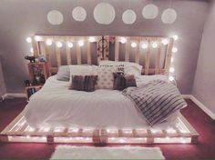 Un lit en palettes avec des guirlandes lumineuses.