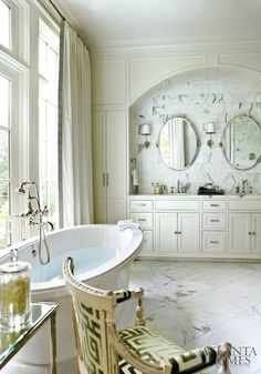 """Marble floors and backsplash, an oval free standing tub, polished nickel sconces, a French chair with Greek key fabric, and silk curtains with Greek key trim."""