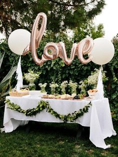 They're not technically hanging centerpieces...but balloons are a great decoration for tables! This outdoor wedding reception table used rose gold Mylar balloons and greenery to spell out the love. These floating decorations are a great way to enhance simple table centerpieces like the mason jar vases here.