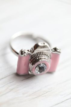 Pink Camera Ring! I want this so bad! my very first and favorite camera was this shade of pink!!! love love love
