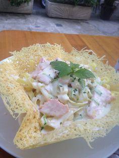Spaguethi con salsa blanca, salmon y en una canasta de queso parmesano