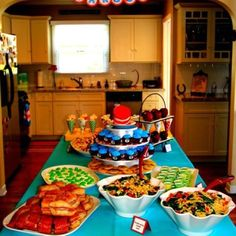 Dr. Seuss party food table Poodles eating noodles salad, green eggs & ham, cat in the hat fruit sticks, hop on pop corn, ten apples up on top, green oobleck jello, star belly sneetch cookies, thing 1 & thing 2 cupcakes, cat in the hat smash cake