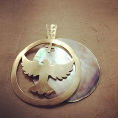 Pingente em prata com banho de ouro com Divino Espirito Santo, madrepérola e zircones no aro.