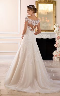 From Stella York, this off-the-shoulder lace wedding dress with sleeves is one-of-a-kind! Lace and tulle over Royal organza in a modern, modified A-line silhouette is a traditional take on a classic bridal look. The illusion lace back is complemented by illusion sleeves in an off-the-shoulder neckline, giving the front and back of the dress added drama. The lace motif continues onto the full tulle skirt creating a waterfall effect down through the train. Diamante beading throughout the gown…