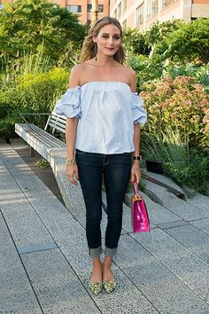 Olivia Palermo wears an off-the-shoulder blue top, cuffed jeans, and floral ballet flats