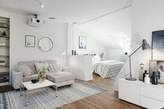 laminate floor inside big room, studio apartment ideas, white walls and a faded rug, bed and sofa, mirror and artworks One Room Apartment, Apartment Layout, Apartment Interior, Apartment Living, Apartment Ideas, Studio Apartment Design, Studio Apartment Decorating, White Studio Apartment, Small Space Living