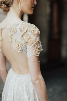 The beading on this wedding dress if sophisticated and gorgeous. We love the way it is draped off the fabric and onto the back!