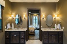 Master bathroom with double vanity and oval mirrors flanked by sconces. Dream bathroom! Fluff Interior Design - Decorating for REAL life! Best of Omaha, NE.