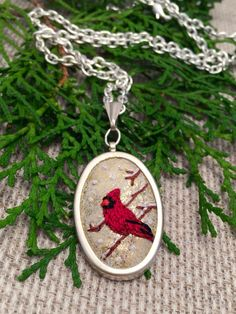 This is so festive and sweet! A tiny red Cardinal, snowy branches and falling snow have been hand embroidered on a shimmery gold metallic wool blend felt, set in a silver pendant.