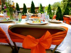 Use cheap plastic table cloths cut into strips to make bows on the chairs. Super cute and affordable.