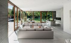 The sun-splashed open living area is framed by floor-to-ceiling Duratherm doors and windows | archdigest.com