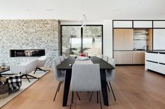 Pale-toned oak was used for flooring and cabinetry. In many areas, the team paired white finishes with black accents. Indoor Slides, Charred Wood, Kitchen Dining, Dining Table, Japanese House, Modern Materials, Residential Architecture, Kitchen Interior, Utah