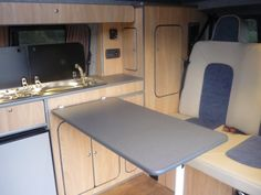 VW T5 campervan conversion interior layout showing rear seats, cooking area and table