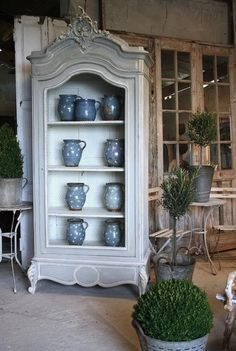 Gray-washed cabinet w/chicken wire. Great way to showcase a collection.