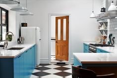 Sustainable Kitchens - Industrial Kitchen with American Diner Feel. St Giles Blue, Farrow & Ball painted flat panel cabinets with routed pulls sit next to a white Smeg fridge. Clearwater Stereo double bowl sink and monobloc tap sourced by client. Bianco venato granite worktops and attached breakfast bar offset the white shelving on vintage Duckett design brackets attached to white metro tiles with dark grout. The checkered floor gives the kitchen a playful feel.