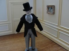 unknown artist porcelain groom wearing gray pants with a black tuxedo coat. He wears a white shirt with a gray cravat. He has molded black hair and wears a tall black hat on his head. sold on ebay for $129