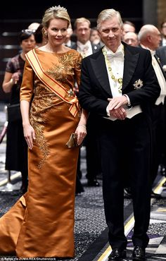 The queen was pictured in a floor length bronze dress decorated with intricate detailing a...