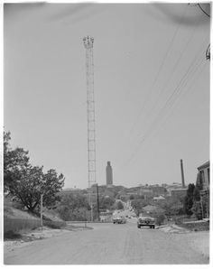 A moonlight tower beside a street that leads towards UT Tower. There are several cars and buildings further down the road.