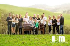 Group photo in grassy field. Beautiful posing ideas for large families.  Photography by Rikki-Lee Wrightson of Pregnant Memories