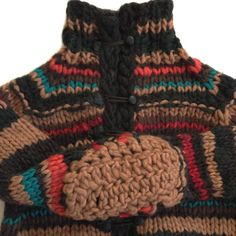 This one of a kind cardigan was handknit on handmade needles using specialty wool yarn of various weights and construction, creating the unique, uneven striped pattern. Truly handcrafted, even the buttons and detailing were created by hand from recycled leather. All of this and the hand crocheted elbow patches make this piece bold--and incredibly warm.