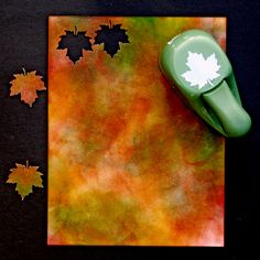 Leaf Template Tutorial by Susan. She used mustard seed, spiced marmalade, Prussian blue, fired brick. Prussian blue is a dark blue, so try chipped sapphire in its place. (The blue will mix with the mustard seed to make green.) After the leaves are punched, edge each with copper ink.