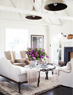 White living room with large purple flower arrangement and traditional fireplace
